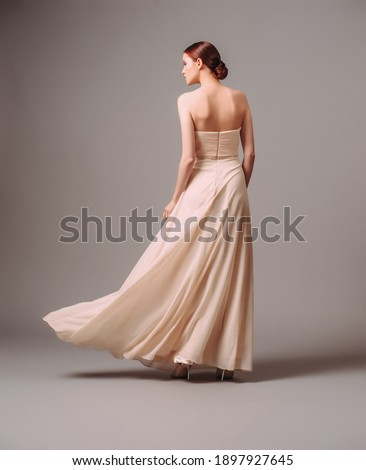 Elegant backless moscato dress. Beautiful pink chiffon evening gown. Studio portrait of young ginger woman. Transformer dress idea for an event. Bridesmaid dresses. Royalty-Free Stock Photo #1897927645