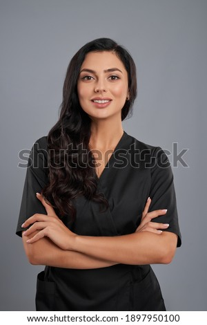 Attractive female beautician in black uniform standing with crossed arms over grey background. Positive cosmetologist with long dark hair smiling and looking at camera. Royalty-Free Stock Photo #1897950100