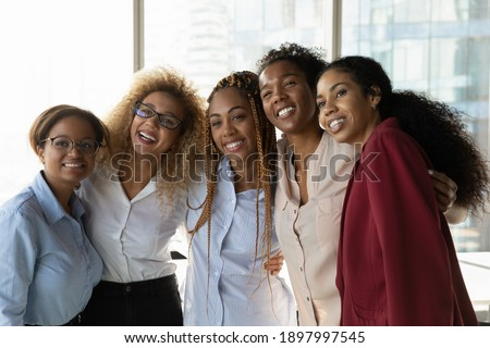 Overjoyed multiethnic diverse female colleagues hug pose for team self-portrait picture together in office. Smiling multiracial women employees make selfie at workplace. Teamwork, success concept.