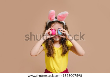 Cute blonde girl kid with rabbit ears holding a mock-up of a tooth. Traditions, discounts, medicine, the concept of the celebration. #1898007598