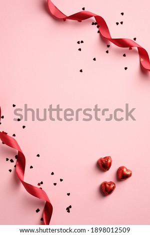 Happy Valentines day card with red ribbon, confetti, heart shaped sweets on pink background. Vertical banner, brochure, poster design. Royalty-Free Stock Photo #1898012509