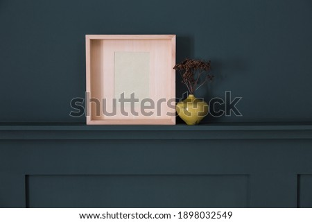 Wooden photo frame and small japanese vase with twigs on paneled wall
