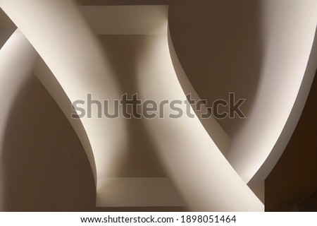 Close-up photo of glowing ceiling structure. Abstract architecture fragment. Modern interior design with curved elements. Geometric composition of curves and surfaces in gray halftones. Royalty-Free Stock Photo #1898051464