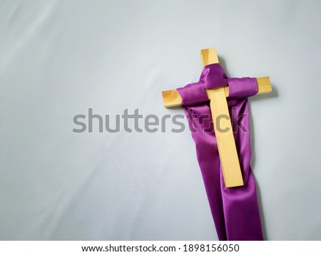 Lent Season,Holy Week and Good Friday concepts - photo of purple cloth cling to wooden cross in vintage white background. Stock photo.