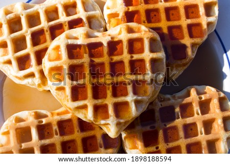 Five classic heart shaped waffles drenched in maple syrup sitting on a white plate with blue trim