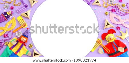 Purim celebration concept (jewish carnival holiday) over wooden purple background. Top view, flat lay