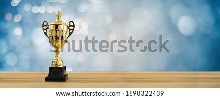 1st champion award, the best prize and winner concept, championship cup or winner trophy on wood table with soft blue and bokeh background Royalty-Free Stock Photo #1898322439