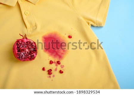 close up yellow T shirt with dirty stain. daily life dirty stain for wash and clean concept. High quality photo Royalty-Free Stock Photo #1898329534