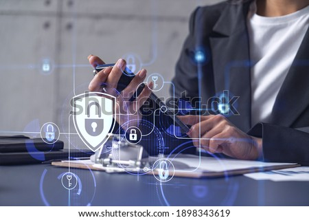 A businesswoman in formal wear checking the phone to sign the contract to prevent probability of risks in cyber security. Padlock Hologram icons over the working desk.
