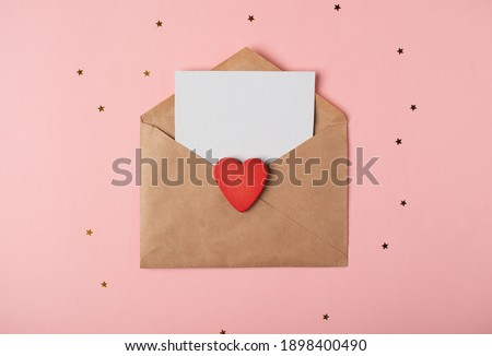 Craft envelope with a blank sheet of paper inside and red wooden heart on the rose background. Romantic love letter for the Valentine's day concept. Space for text.