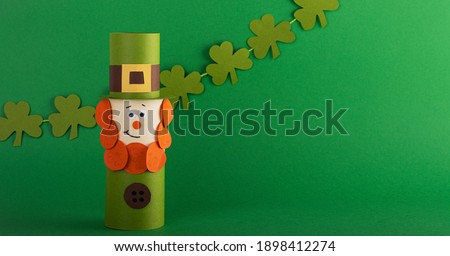 Green cute Leprechaun made of handmade paper with four-leaf clover on a green background, space for text. Cultural and religious holiday St. Patrick's Day