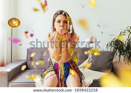 Brazilian Carnival. Young woman enjoying the carnival at home blowing confetti Royalty-Free Stock Photo #1898422258
