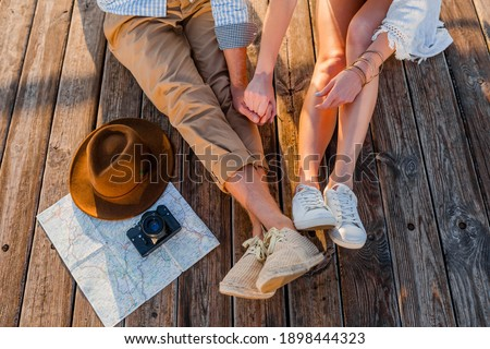 view from above legs of couple traveling in summer dressed in sneakers, man and woman boho hipster style fashion having fun together, map, hat, photo camera, sightseeing, footwear fashion Royalty-Free Stock Photo #1898444323