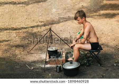 A 12-year-old boy is sitting by a fire in nature, cooking dinner in a saucepan over a real fire. Camping kitchen. A child without clothes on a hike in hot summer. High quality photo