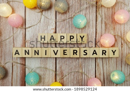 Happy Anniversary alphabet letter with LED cotton balls on wooden background Royalty-Free Stock Photo #1898529124