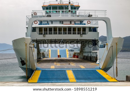 a ferry has docked in the port and is waiting for passengers and cars with an open loading ramp. Royalty-Free Stock Photo #1898551219