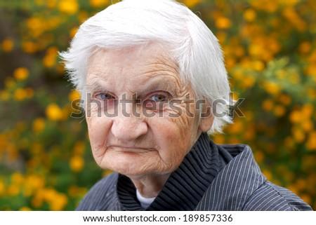 Portrait of an elderly woman walking in the garden #189857336