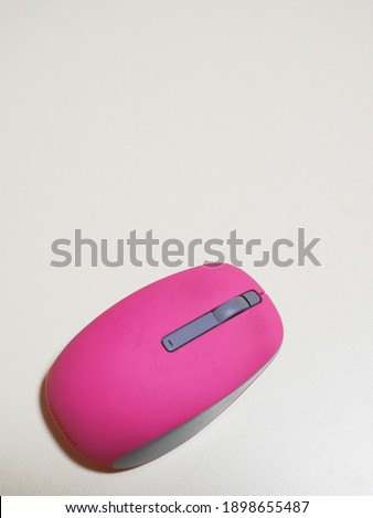This is a picture of a pink mouse. This is a vertical image.