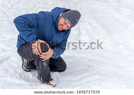 Photo of injured young man bend down on snow and holding his knee in pain, outdoor. Young man holding his knee in pain on a snowy cold winter day. Man having a knee injury on winter road. Copy space.