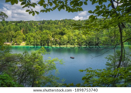 Lake and paddleboat framed by tree branches and green forest illuminated by sunlight in Plitvice Lakes National Park UNESCO World Heritage in Croatia #1898753740