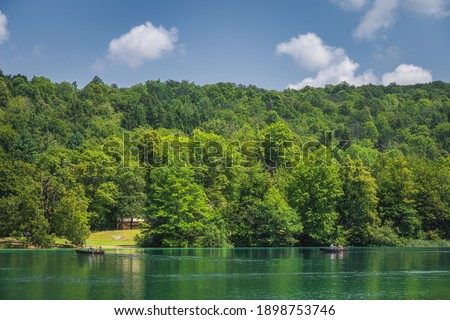 Tourists paddling in two paddleboats on emerald green lake in Plitvice Lakes National Park UNESCO World Heritage in Croatia #1898753746