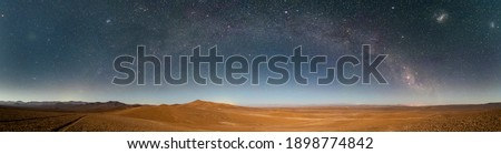 An amazing panoramic view of the Milky Way above Atacama Desert vast sand fields. An awe night sky view with our galaxy arm creating an arch in between the stars. An idyllic and motivational scenery Royalty-Free Stock Photo #1898774842