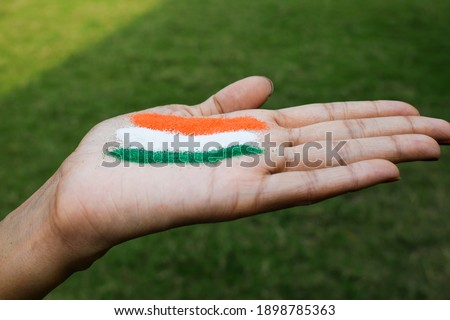 Girl putting rangoli on palm on occasion of Indian republic day celebration at home lockdown. Tri color Indian flag tattoo design depicting freedom, unity and written constitution