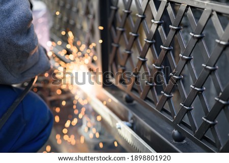 Welding the steel gear racks to gate. Last phase before setting up an automated gate operator. Professional service of installation and maintenance of automatic cantilever sliding gate. Royalty-Free Stock Photo #1898801920