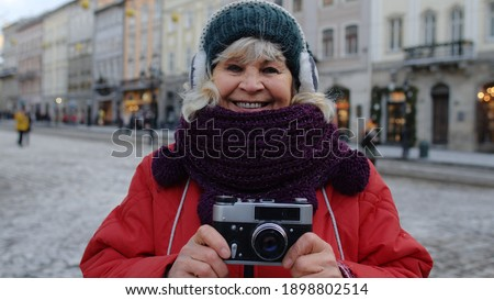 Portrait of senior woman tourist taking pictures with photo camera, looking at camera using retro device in winter city center of Lviv, Ukraine. Photography, travelling, vacation. Active pensioner