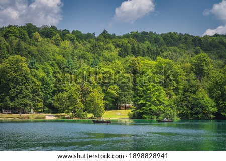 Tourists paddling in two paddleboats on emerald green lake in Plitvice Lakes National Park UNESCO World Heritage in Croatia #1898828941
