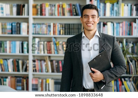 Portrait of handsome successful hispanic man dressed in formal stylish suit and looking directly at the camera. Confident business mentor, manager or entrepreneur Royalty-Free Stock Photo #1898833648
