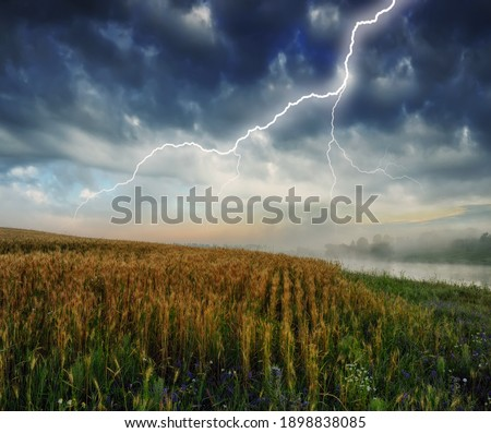 lightning over a hilly field. landscape with dramatic thunderclouds in the background