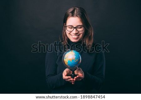 Photo of cute young woman holding globe and smiling over dark background