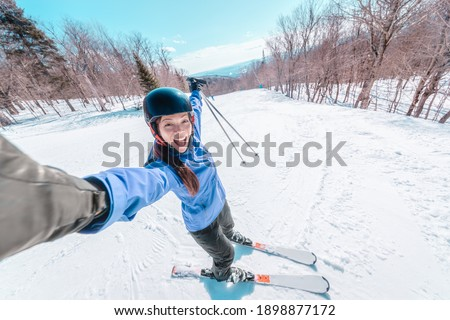Ski selfie happy skier woman screaming of joy skiing on ski resort slopes with arms up in fun. Asian girl wearing winter jacket, helmet, gloves, boots and skis.