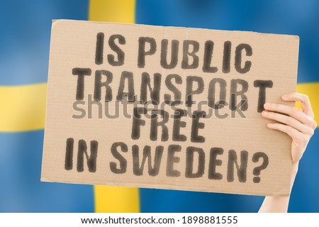 """The quesiton """" Is public transport free in Sweden? """" on a banner in men's hand with blurred Swedish flag on the background. Transportation. Money. Cheap. City. Urban"""