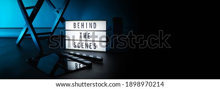 Behind the scenes letterboard text on Lightbox or Cinema Light box. Movie clapperboard megaphone and director chair beside. Background LED color change loop. static camera in video production studio.