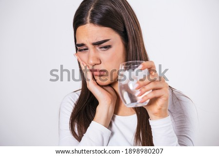 Young woman with sensitive teeth and hand holding glass of cold water with ice. Healthcare concept. woman drinking cold drink, glass full of ice cubes and feels toothache, pain