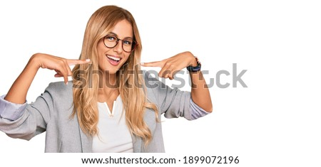 Beautiful blonde young woman wearing business clothes smiling cheerful showing and pointing with fingers teeth and mouth. dental health concept.