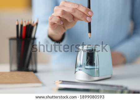 Female hands sticking out pencil in electronic sharpener closeup. Design project development concept Royalty-Free Stock Photo #1899080593