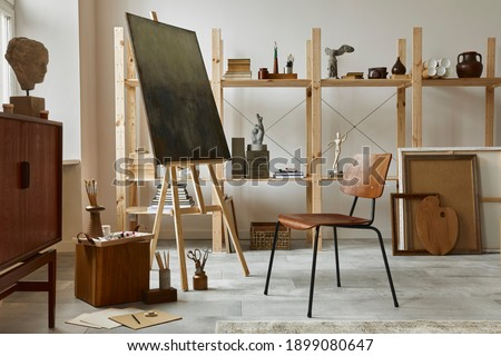 Unique artist workspace interior with stylish teak commode, wooden easel, bookcase, artworks, painting accessories, decoration and elegant personal stuff. Modern work room for artist. Template. Royalty-Free Stock Photo #1899080647