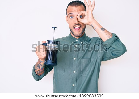 Young handsome man with tattoo holding french coffee maker smiling happy doing ok sign with hand on eye looking through fingers