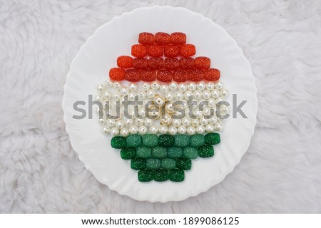 Jewelry beads ruby emerald colored represented Indian flag for Indian republic day celebration on 26 january. Beaded wallpaper decoration colors of India