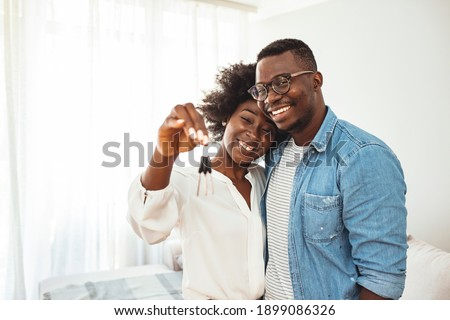Happy young family couple holding key to new home on moving day concept, first time real estate owners man husband embrace woman wife look at camera proud buying property stand in own flat with boxes Royalty-Free Stock Photo #1899086326