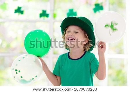 Family celebrating St. Patrick's Day. Irish holiday, culture and tradition. Kids wear green leprechaun hat and beard with Ireland flag and clover leaf. Children having fun at St Patrick party. Royalty-Free Stock Photo #1899090280