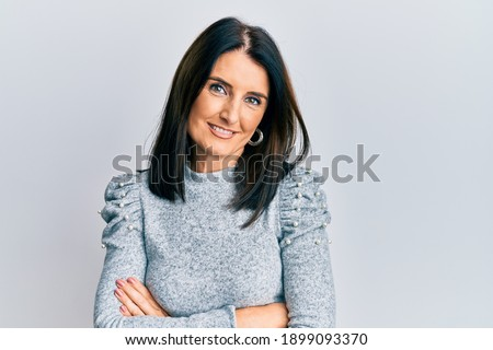 Middle age brunette woman wearing casual clothes happy face smiling with crossed arms looking at the camera. positive person.  Royalty-Free Stock Photo #1899093370