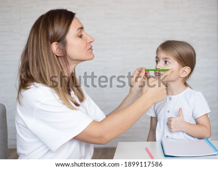 Speech therapy with a toddler. Woman and child doing exercise for children with speech language delays. Royalty-Free Stock Photo #1899117586