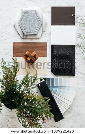 Top view of Material Selections including Granite tile, Marble tile, Acoustic tile, Walnut and Ash Wood Laminate and Painted color swatch with plant and flowers on marble top table.
