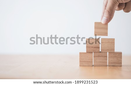 Hand putting and stacking blank wooden cubes on table with copy space for input wording and infographic icon.