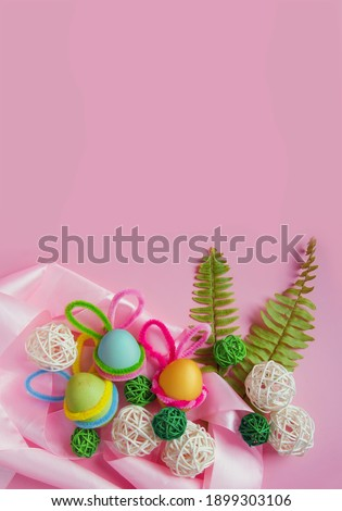 Happy Easter. Easter campaign of colorful eggs with bunny ears, leaves, ornaments and ribbons on a pink background. Vertical banner. View from above. Easter card. Horizontal format, banner. Copyspace