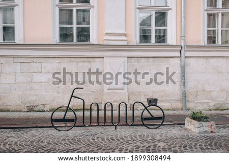 The bike rack is made of metal in the shape of the bike itself. Lviv, Market Square, Ukraine. Street of Eastern Europe. Royalty-Free Stock Photo #1899308494